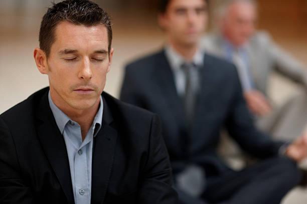 Junge business Mann Meditieren mit Kollegen in den Rücken – Foto