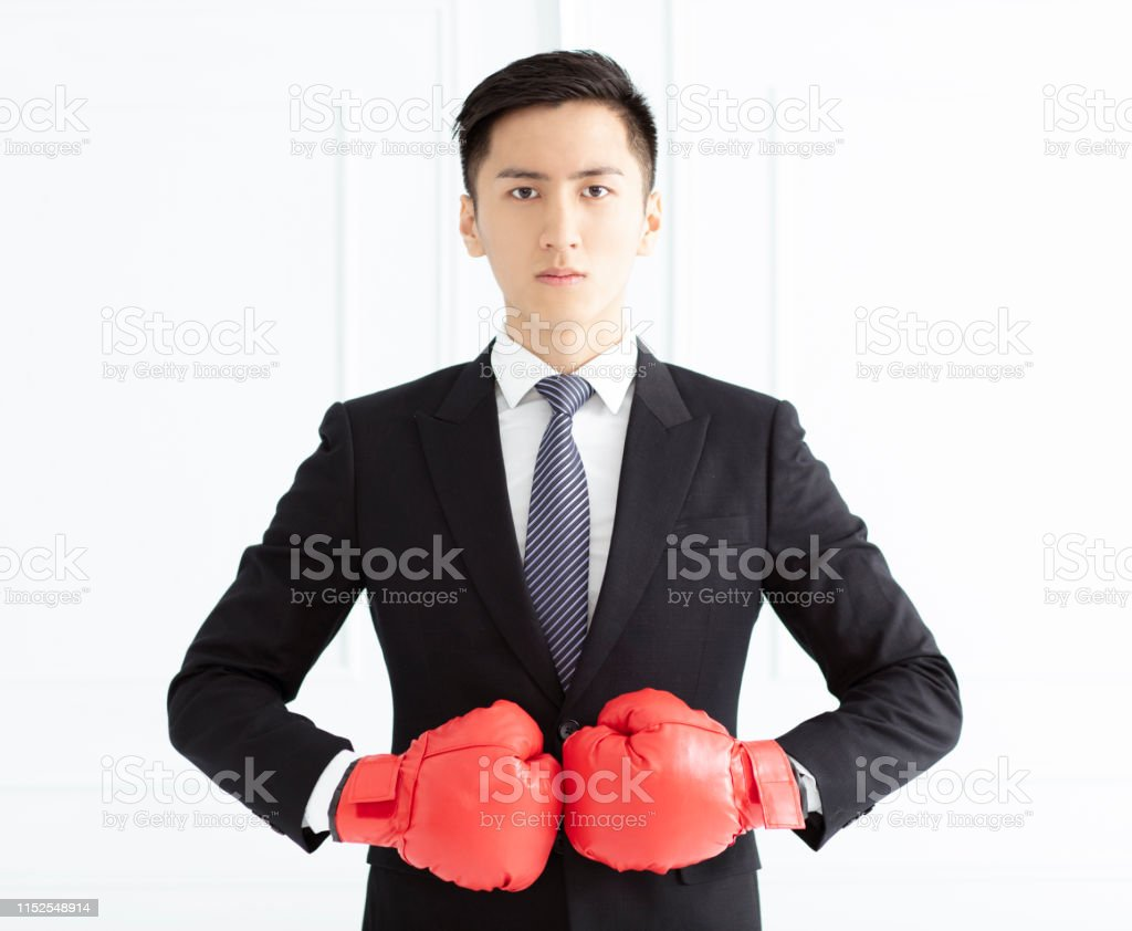 young Business man ready to fight with boxing gloves