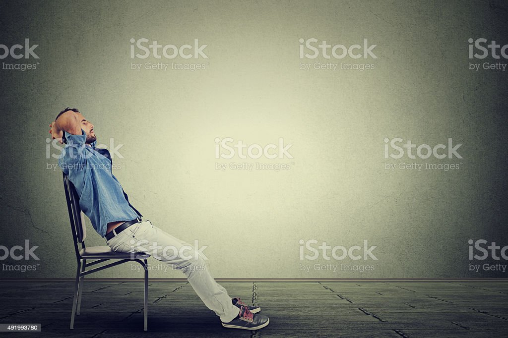 young business man relaxes in his empty office stock photo