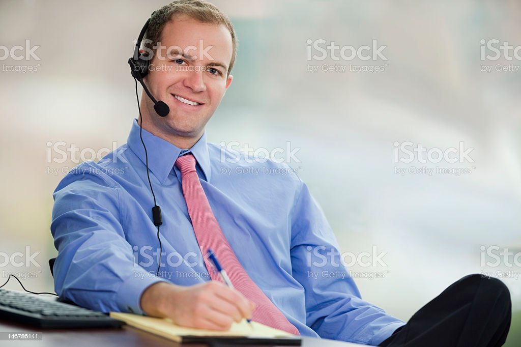Young Business Man Sitting In Office Wearing Headset royalty-free stock photo