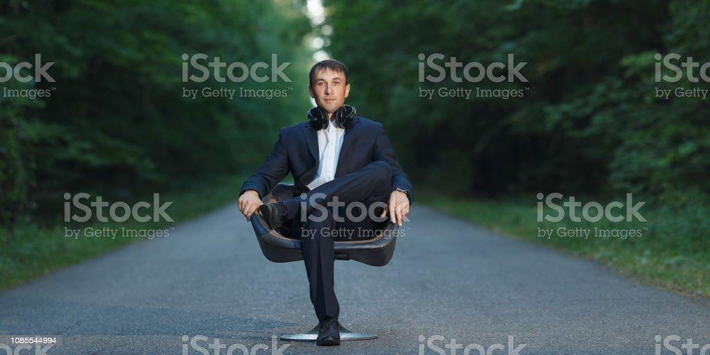 Junger Geschäftsmann sitzen auf Stuhl in Anzug und Kopfhörer im Wald – Foto