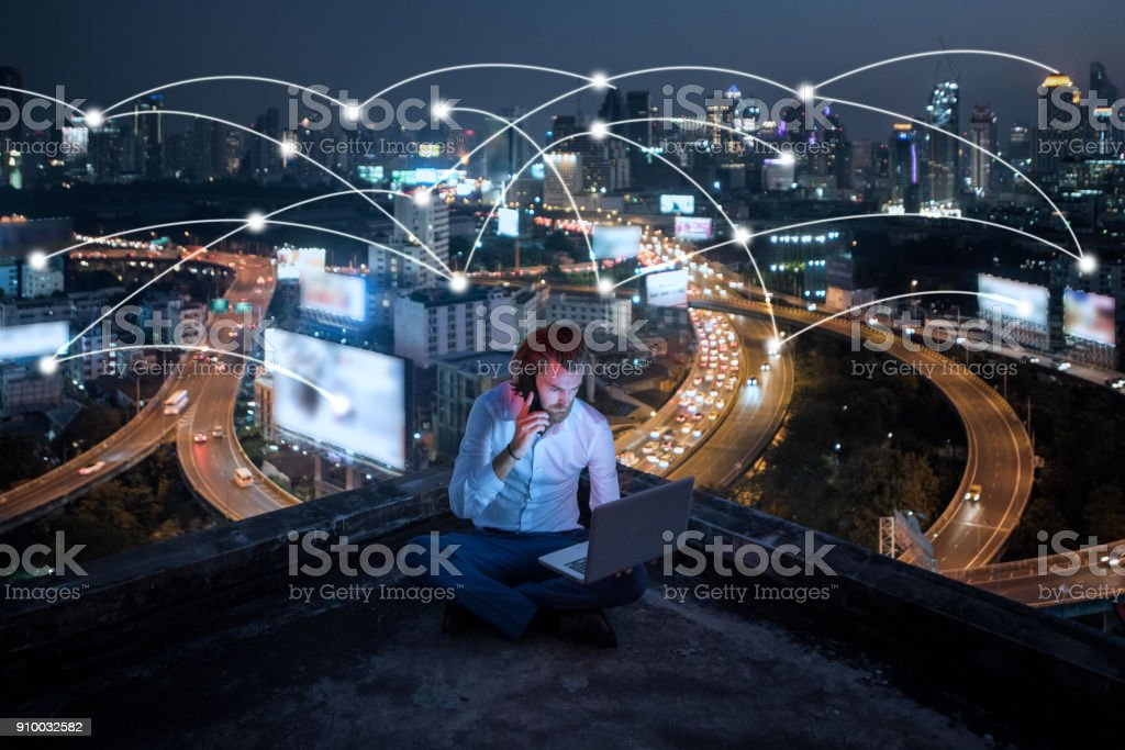 young business man sitting talking mobile phone and working at night on rooftop,business business and network technology concept stock photo