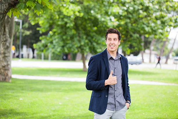 Young Business Man Smiling While Showing Thumbs Up stock photo