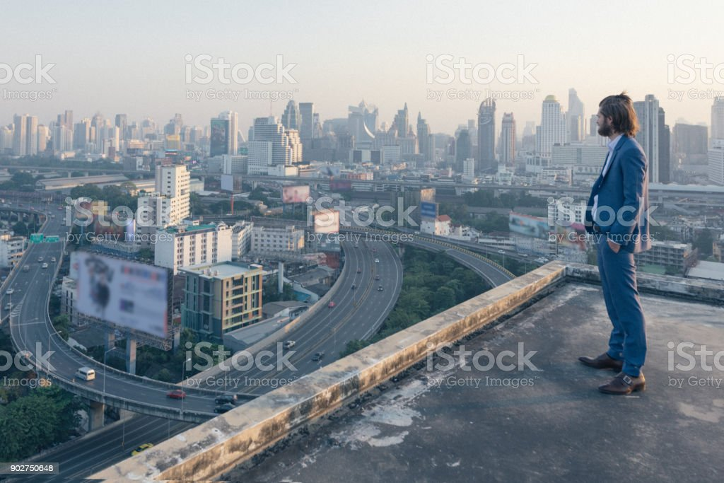 young business man standing on a roof and looking at city stock photo