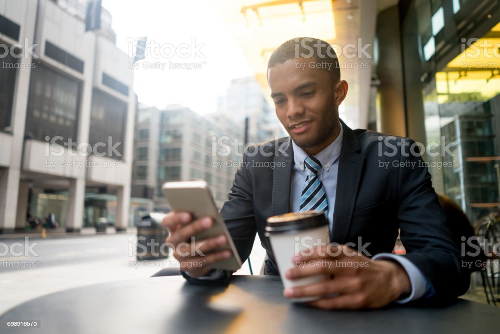 Young business man texting on his phone at a cafe stock photo