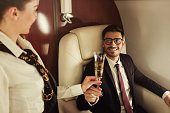 Young business man travelling first class, sitting in suit at table, flight attendant is bringing him glass of champagne to celebrate success