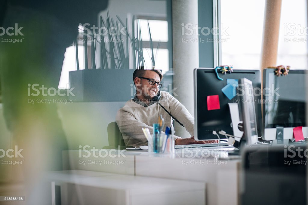 Young business man typing on computer while on phone stock photo