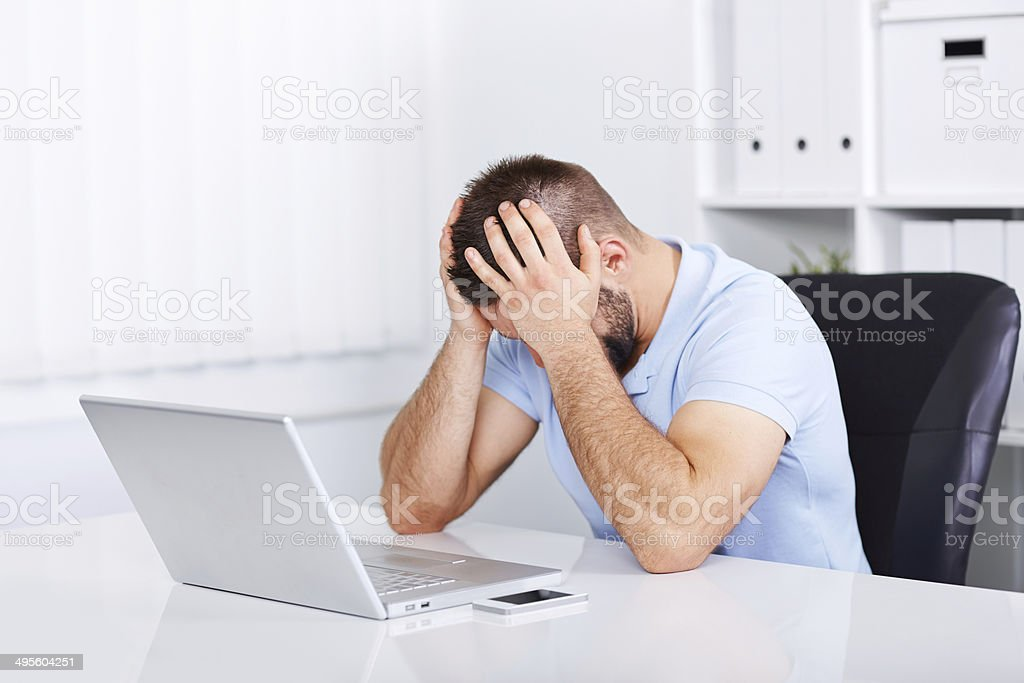 Young business man under stress with headache stock photo
