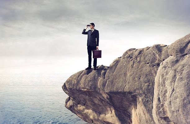 Jeune homme d'affaires à l'aide de jumelles sur la falaise - Photo