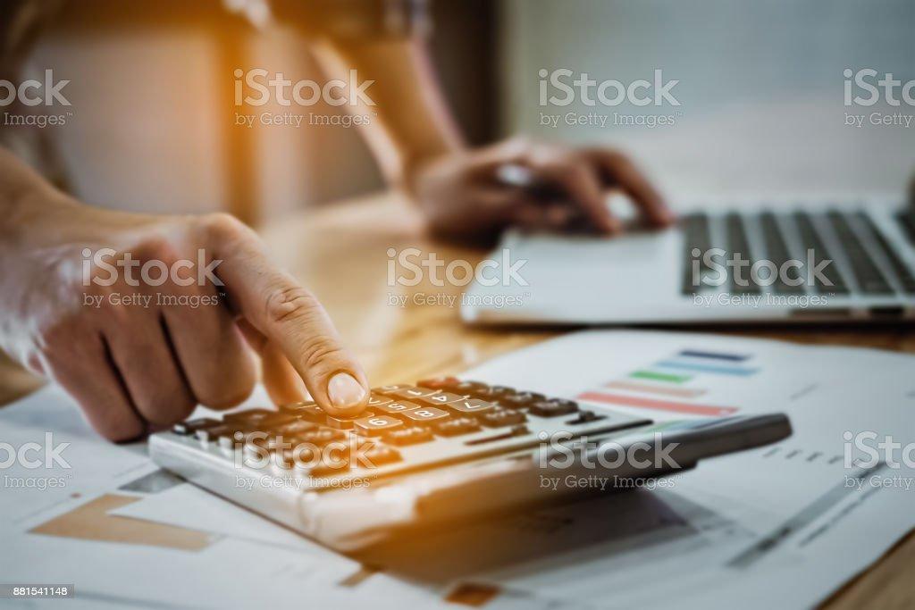 Junger Geschäftsmann mit Rechner und Laptop mit Graph-Diagramm – Foto