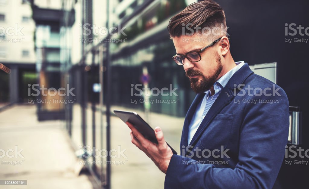 Young business man using digital tablet outdoor. Business, education, lifestyle concept Successful businessman standing in front of the office and using digital tablet. Business, education, lifestyle concept Adult Stock Photo