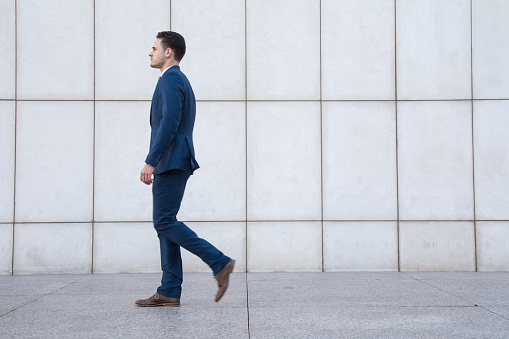 istock Young business man walking in street 889872864