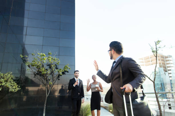 Young business man waving at his team stock photo