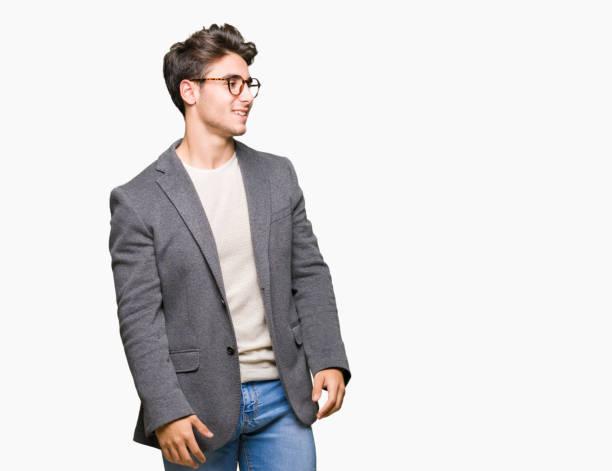 若いビジネス人孤立した背景が笑顔で側に自然な表現の顔に離れて見るメガネを着用します。自信を持って笑っています。 - ジャケット ストックフォトと画像