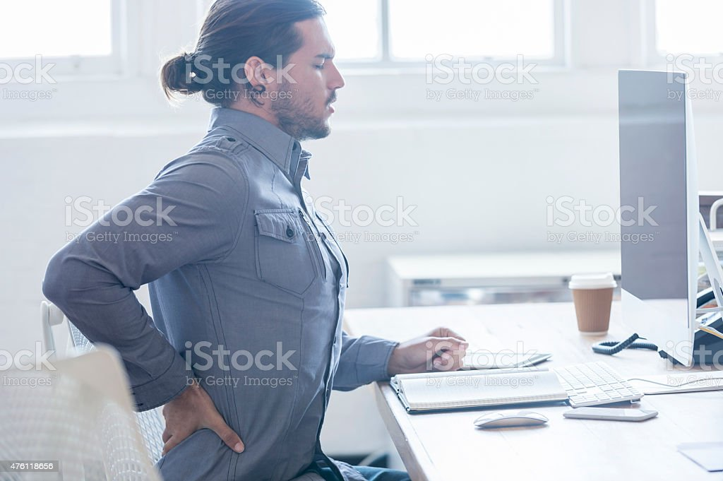 Young business man with holding his back in pain. stock photo