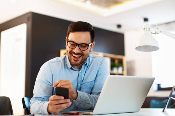 Young business man working at home with laptop and uses a smartphone stock photo