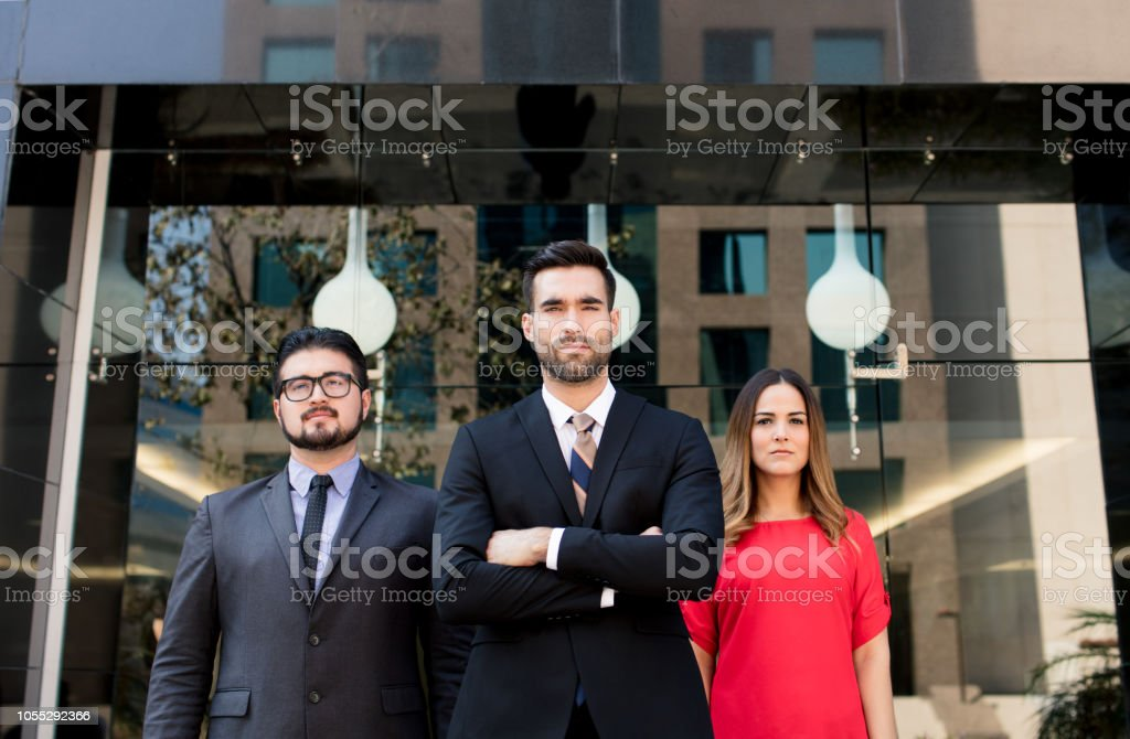 Young business men posing in front of building stock photo