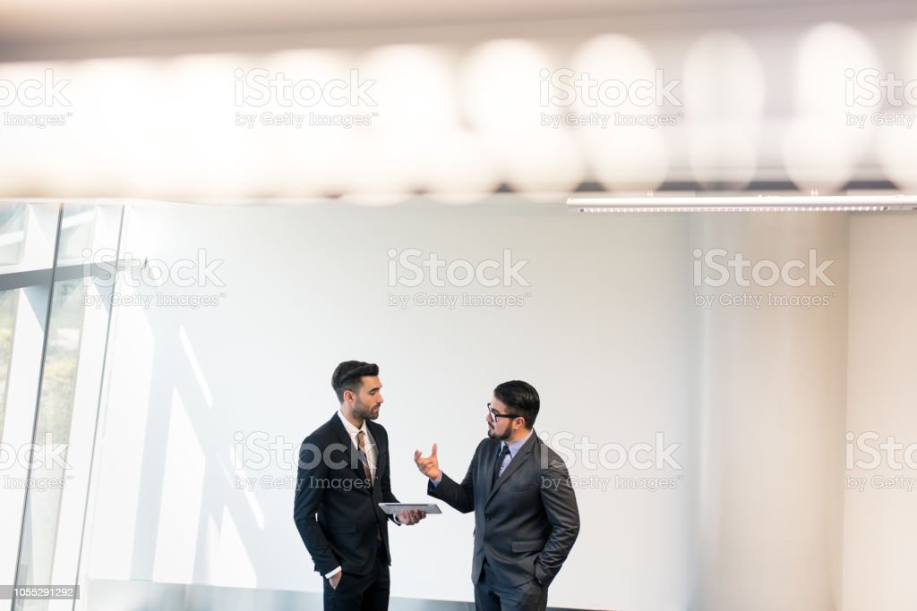 Young business men talking in conference room stock photo