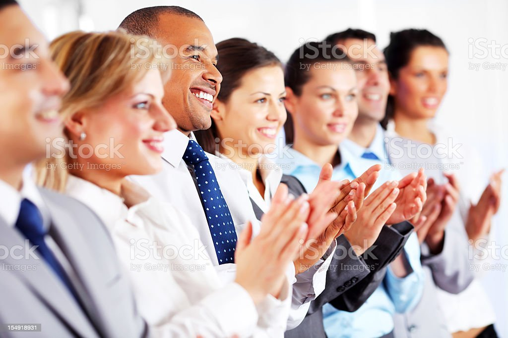 Young business people are standing in the row and applauding. royalty-free stock photo