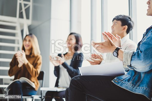 istock Young business people clapping hands during meeting in office for their success in business work 1035507764