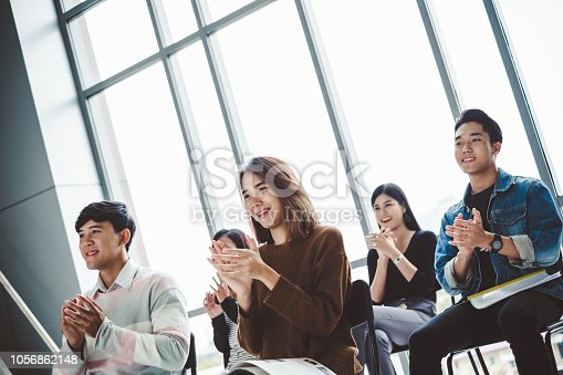 istock Young business people clapping hands during meeting in office for their success in business work 1056862148
