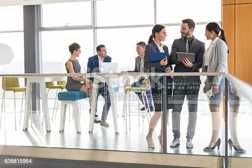 istock Young business people discussing business strategy using digital tablet 626815954