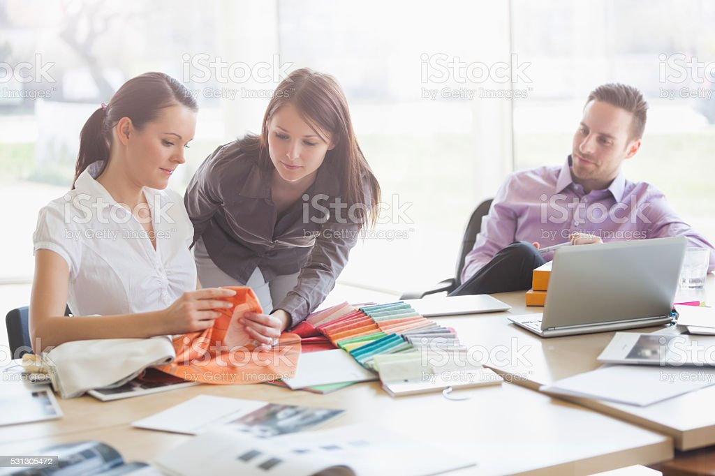 Young business people discussing over fabric swatches at desk stock photo