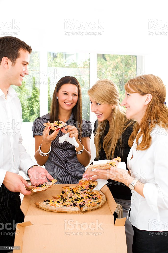 Young business people enjoying a pizza in lunch break royalty-free stock photo