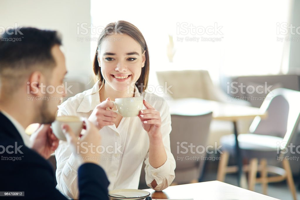 Young business people, man and woman, having friendly talk in cafe. Businessman and businesswoman enjoying networking coffee meeting. Focus on smiling young woman holding cup of coffee royalty-free stock photo