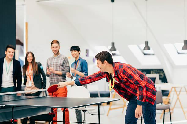 Jovens empresários jogar tênis de mesa em seu escritório - foto de acervo