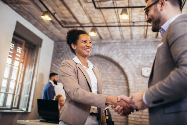 Young business people shaking hands in the office. Finishing successful meeting. stock photo
