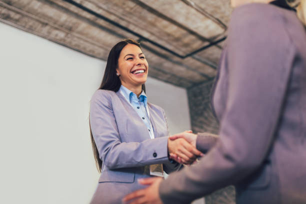 Young business people shaking hands in the office. stock photo