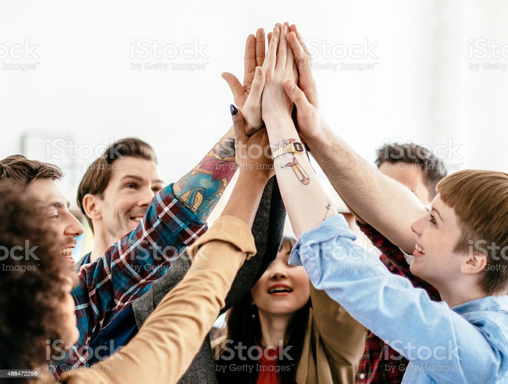 Young Business People Showing Team Spirit With Raised Arms stock photo