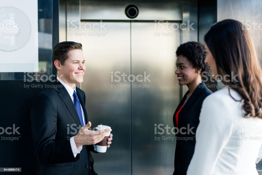 Young business people standing and waiting for the elevator stock photo