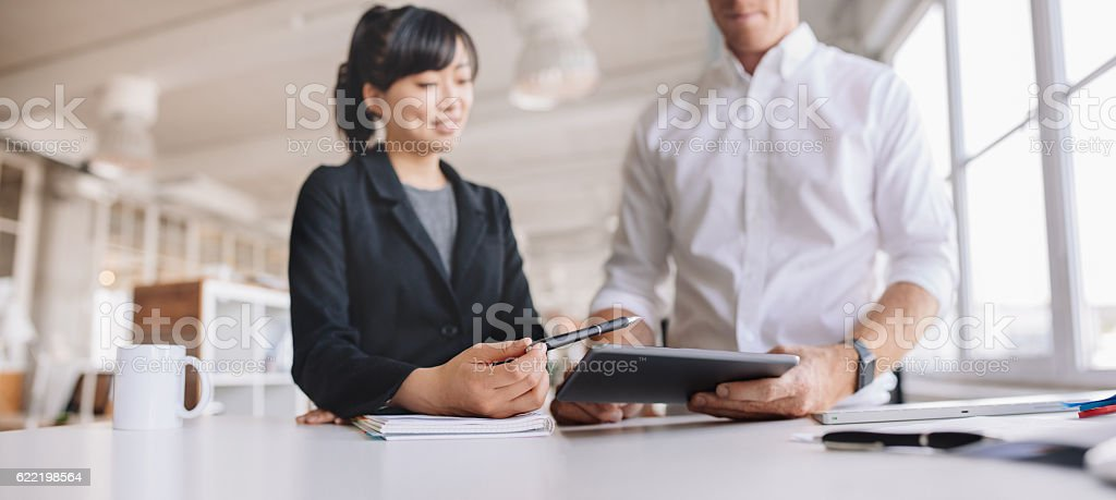 Young business people using digital tablet at work stock photo