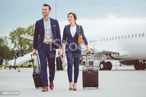 istock Young business people walking in front of airplane 686267538