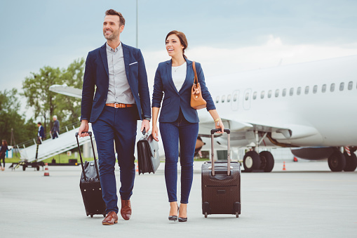 Full length shot of two young business people walking in front of airplane with luggage. People in business trip.
