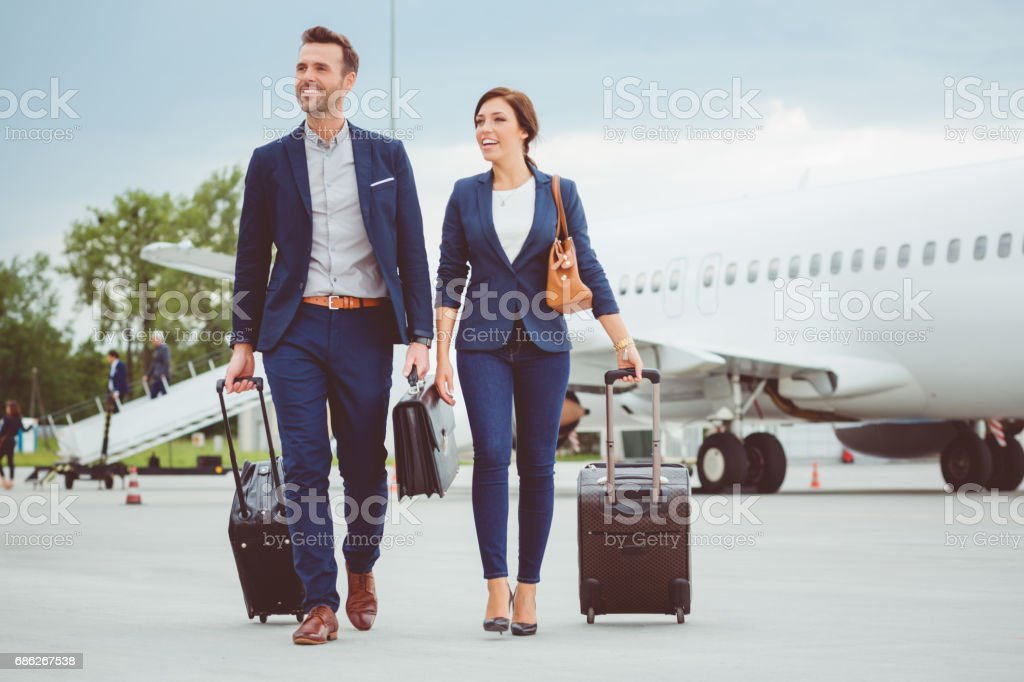 Young business people walking in front of airplane stock photo