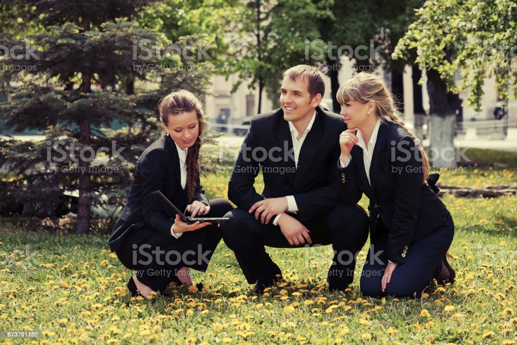 Young business people with laptop in a city park royalty-free stock photo