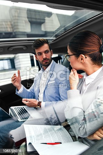 istock Young business people working together while traveling by a car. 1083704316