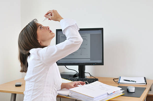 Young business person applying eyes drops stock photo