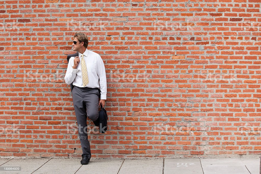 Young Business Professional next to the brick wall stock photo