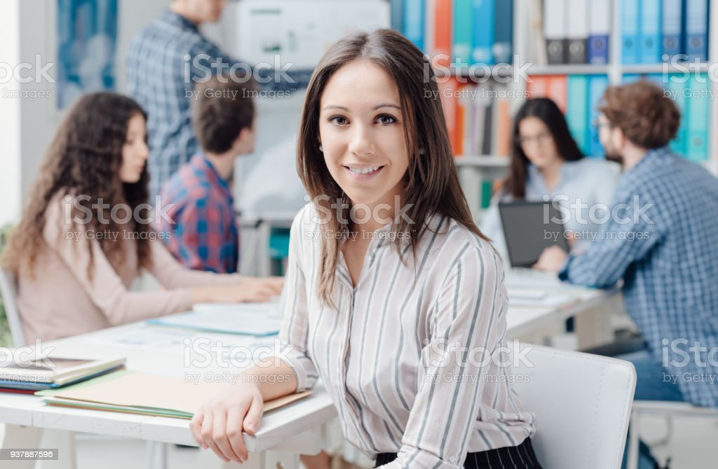 Young business team and girl smiling Young business team meeting in the office and smiling woman posing on the foreground, start up and new business concept Adult Stock Photo