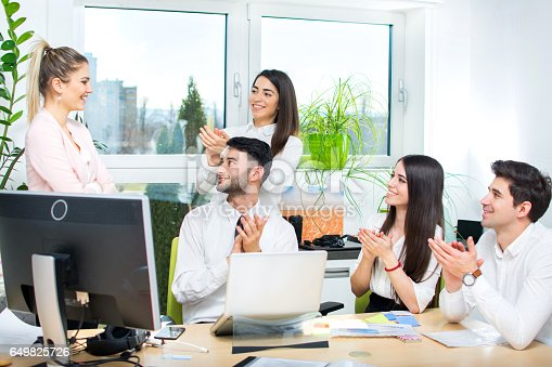 Young business team applauding their colleague in the office.