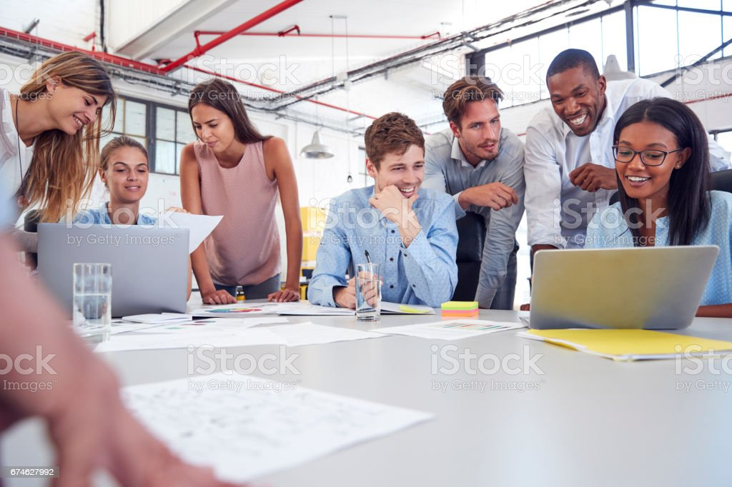 Young business team gathered around two laptops in an office stock photo