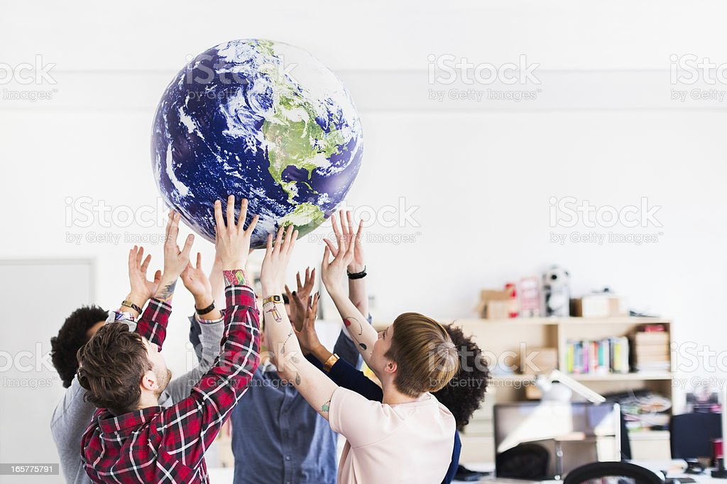 Young Business Team Playing With Earth Globe stock photo