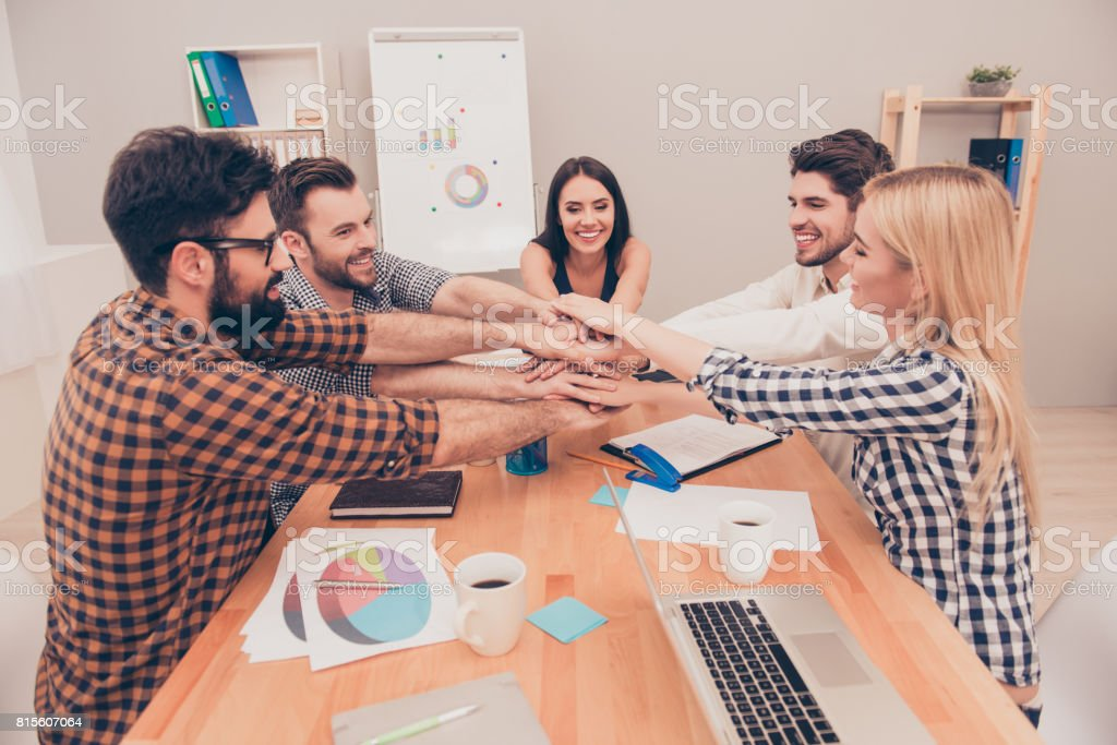 young business team putting their hands on top of each other at conference and smiling stock photo