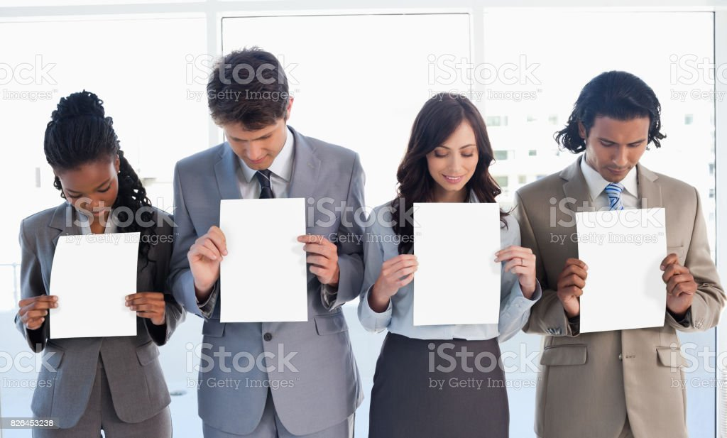 Young business team showing blank sheets while bowing their heads stock photo