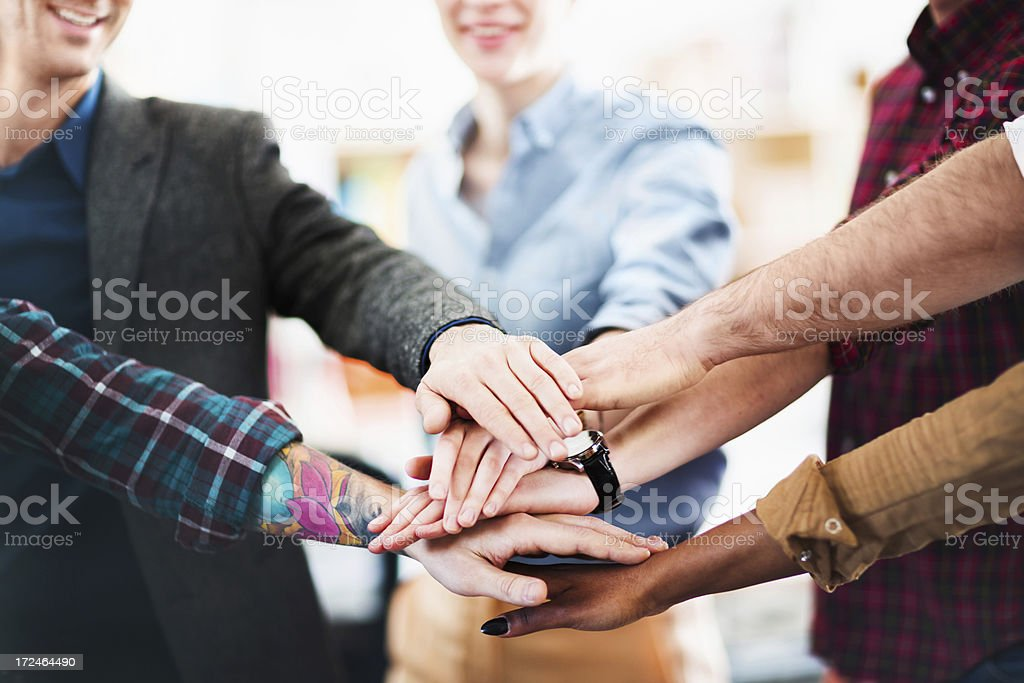 A young business team with hands all in royalty-free stock photo