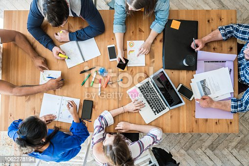 Top view of young business team working together at office. Woman pointing at a chart and explaining the analysis about business strategies.